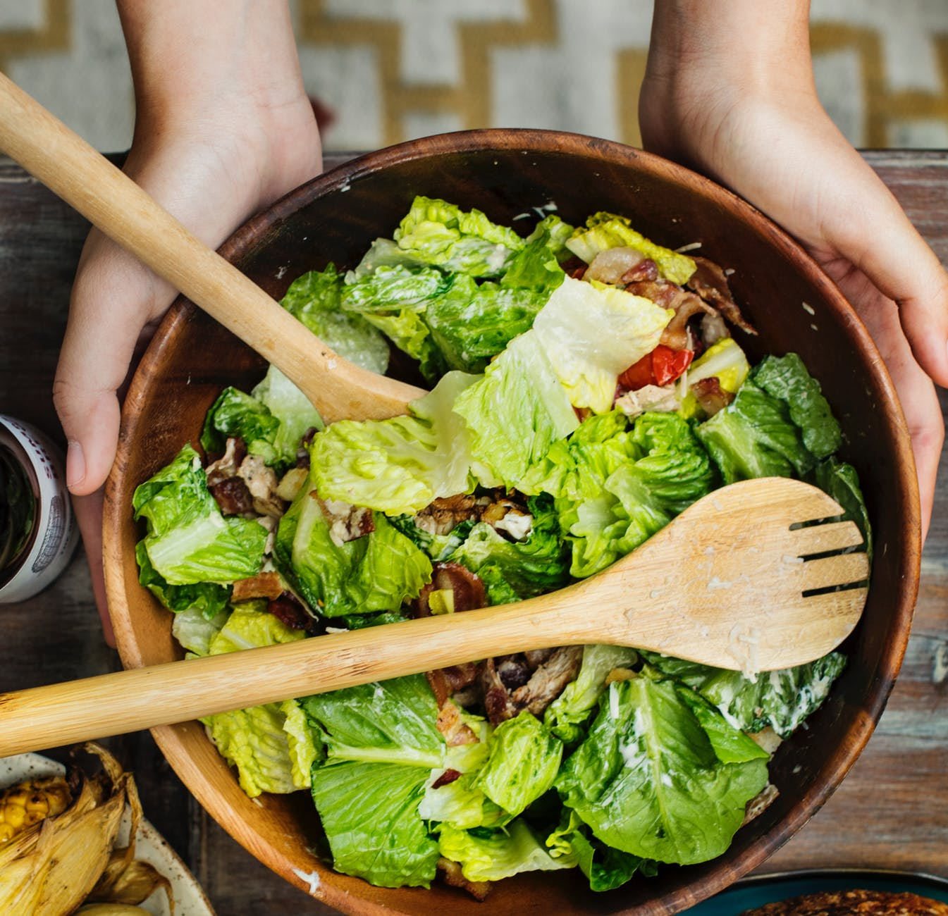 person holding brown wooden bowl with vegetable salad inside